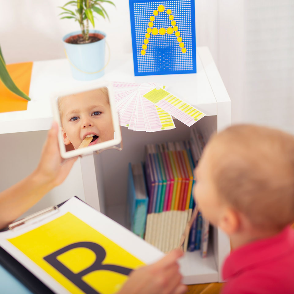 Child looking in the mirror and learning to make an 'r' sound