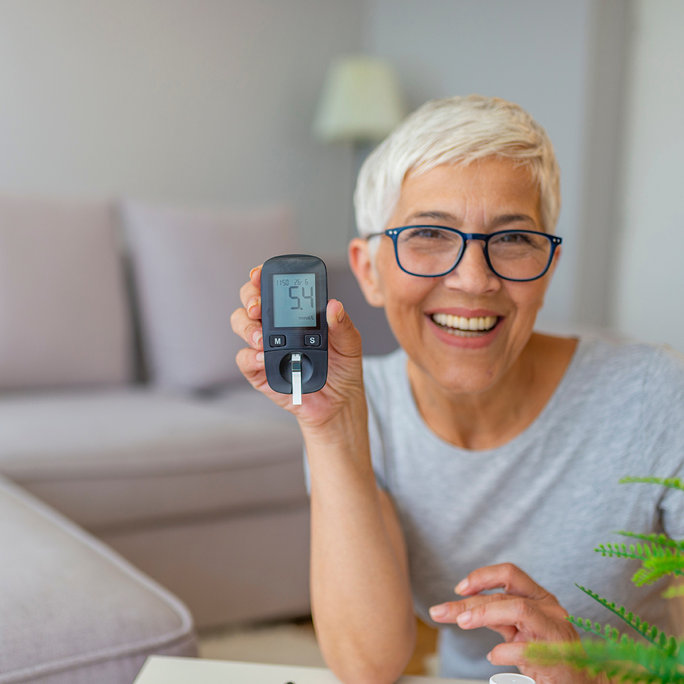 Smiling woman holding up a blood glucose meter