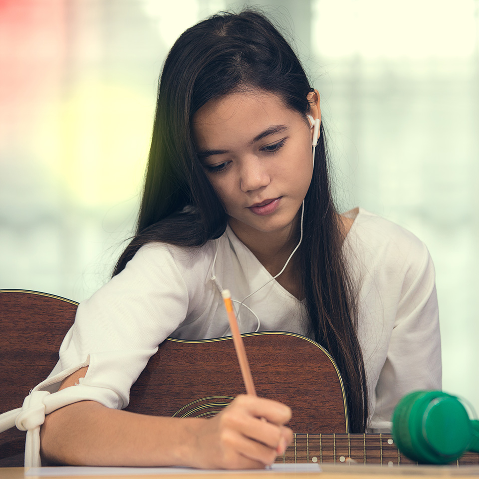 Woman with a guitar under her arm composing music