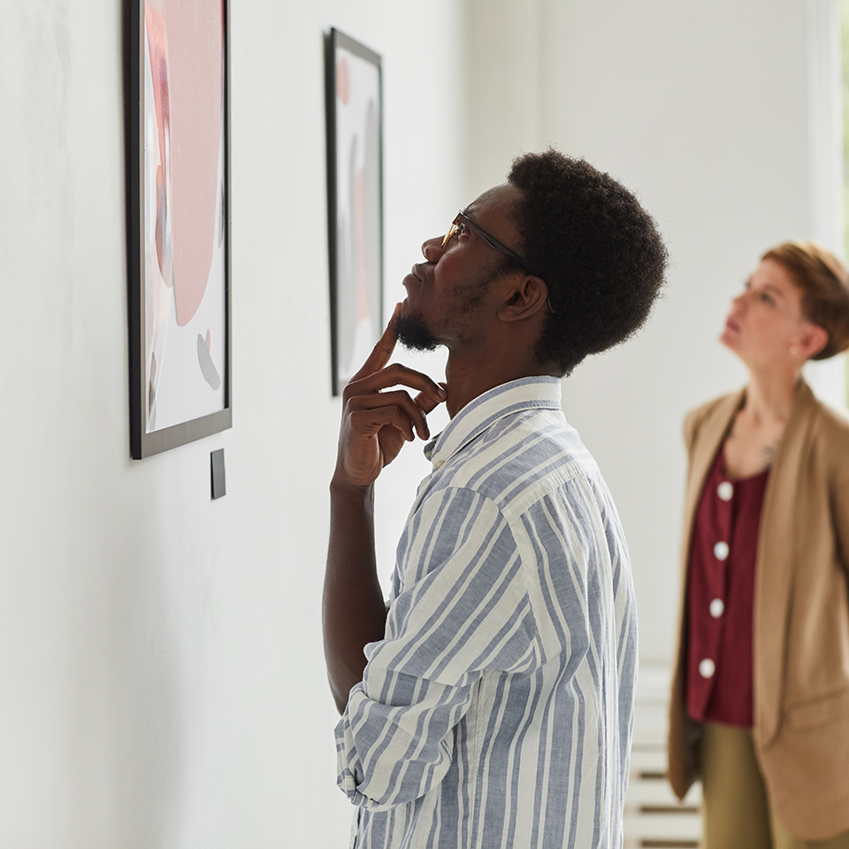 Side view portrait of man looking at paintings while exploring a modern art gallery exhibition