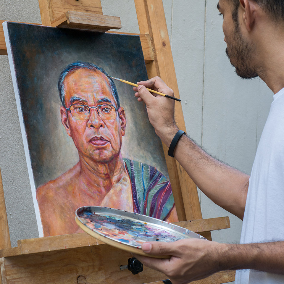 Artist painting portrait of a man using oil colour on a canvas, which is on an easel