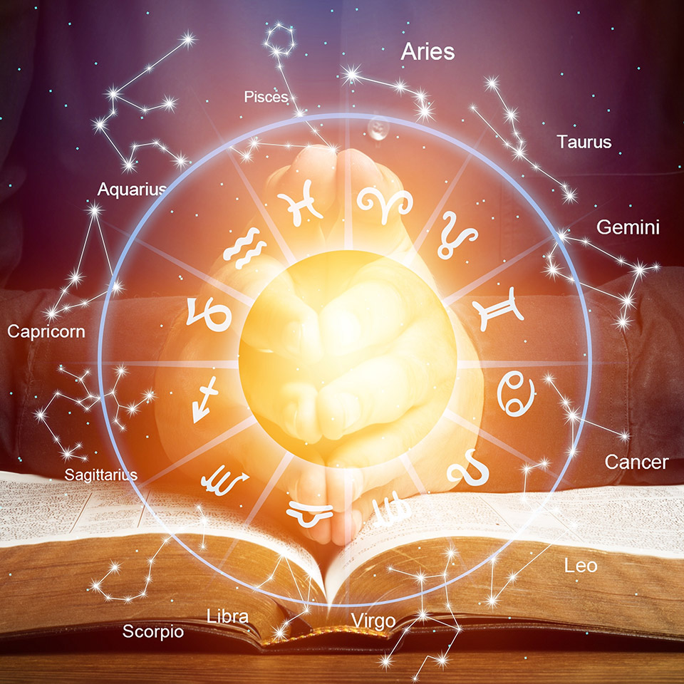 Astrological signs and zodiac symbols surrounding a glowing circle in front or a pair of hands resting on a book