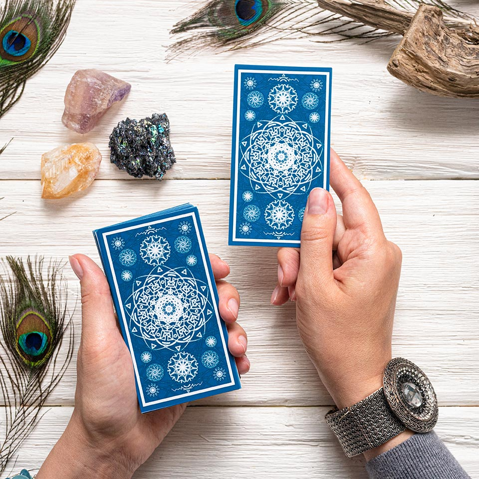 Fortune teller holding blue cards above a white wooden table