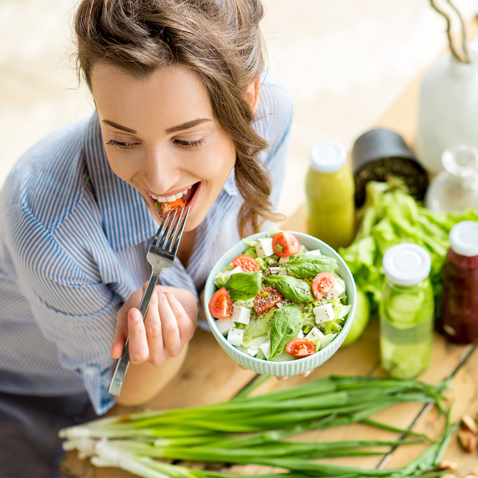 Young and happy woman eating a vegan ketogenic meal