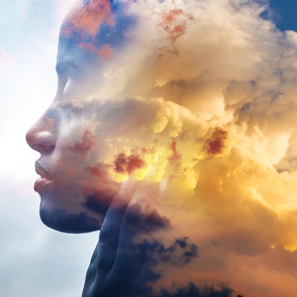 Doube exposed image of a woman's face and clouds backlit by the sun