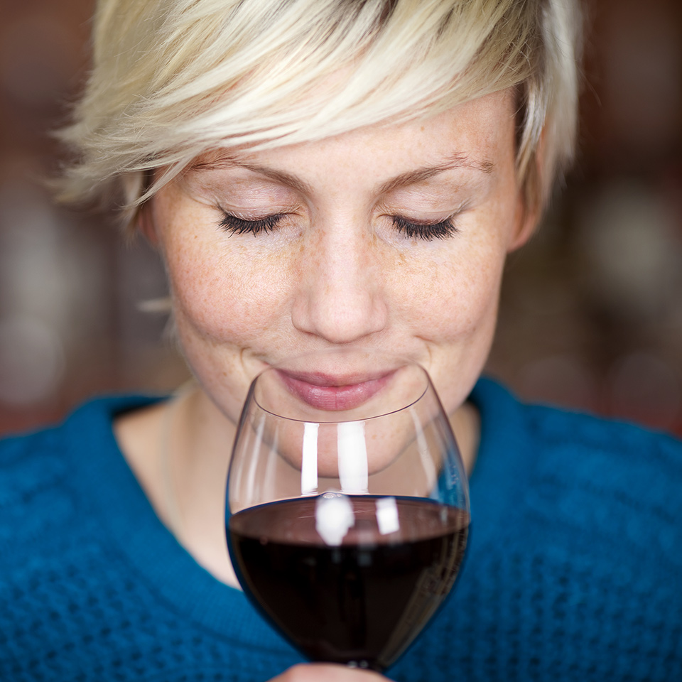 Closeup portrait of a woman sniffing a glass of red wine