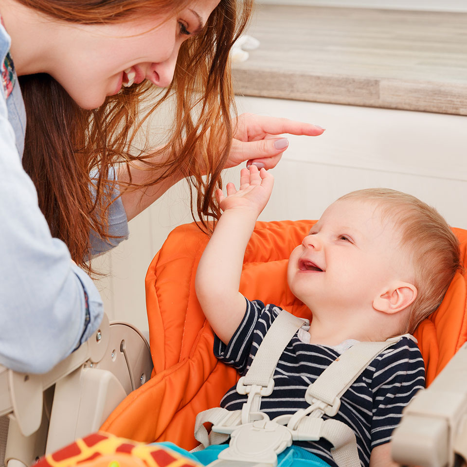Mother and baby using baby sign language to communicate
