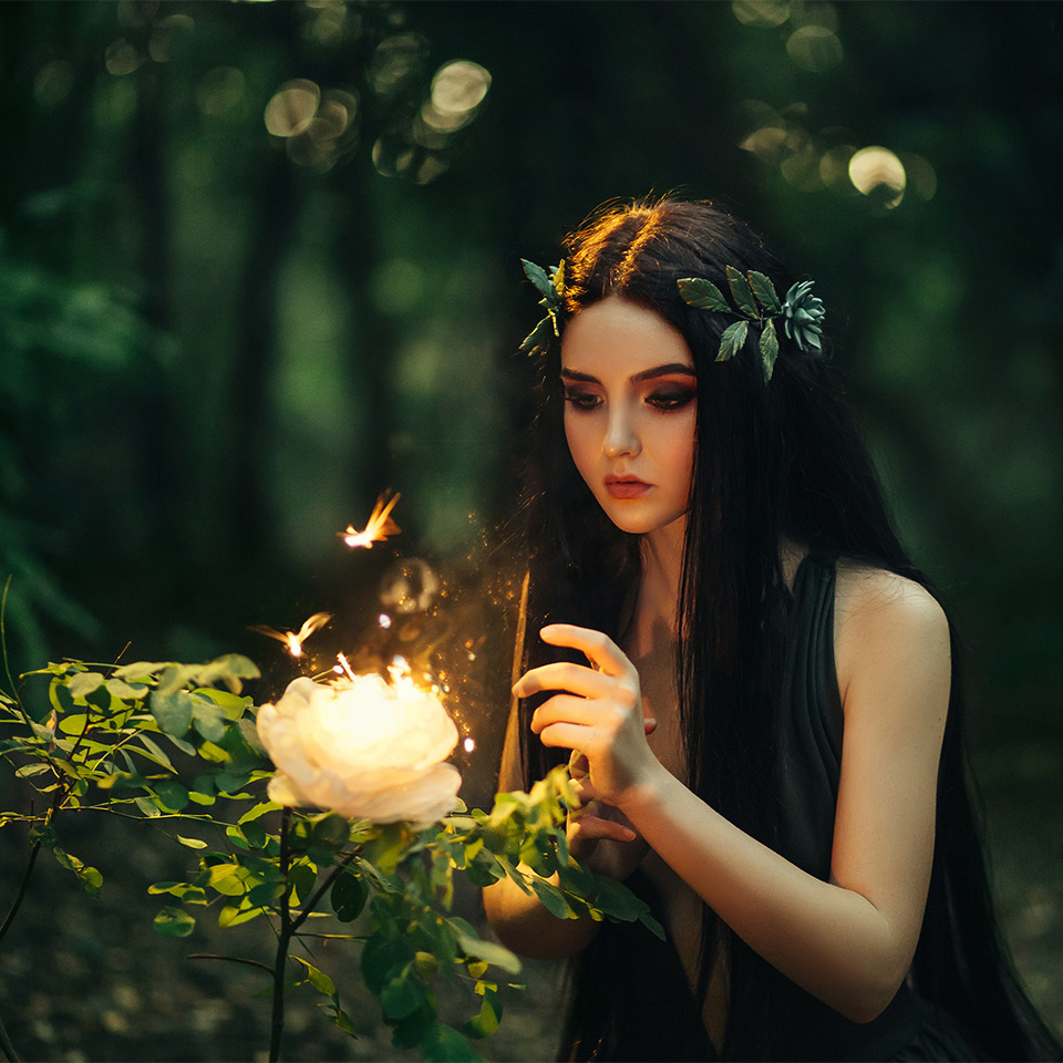 A fairy with long hair in a forest, looking at a flaming, fiery flower surrounded by butterflies.