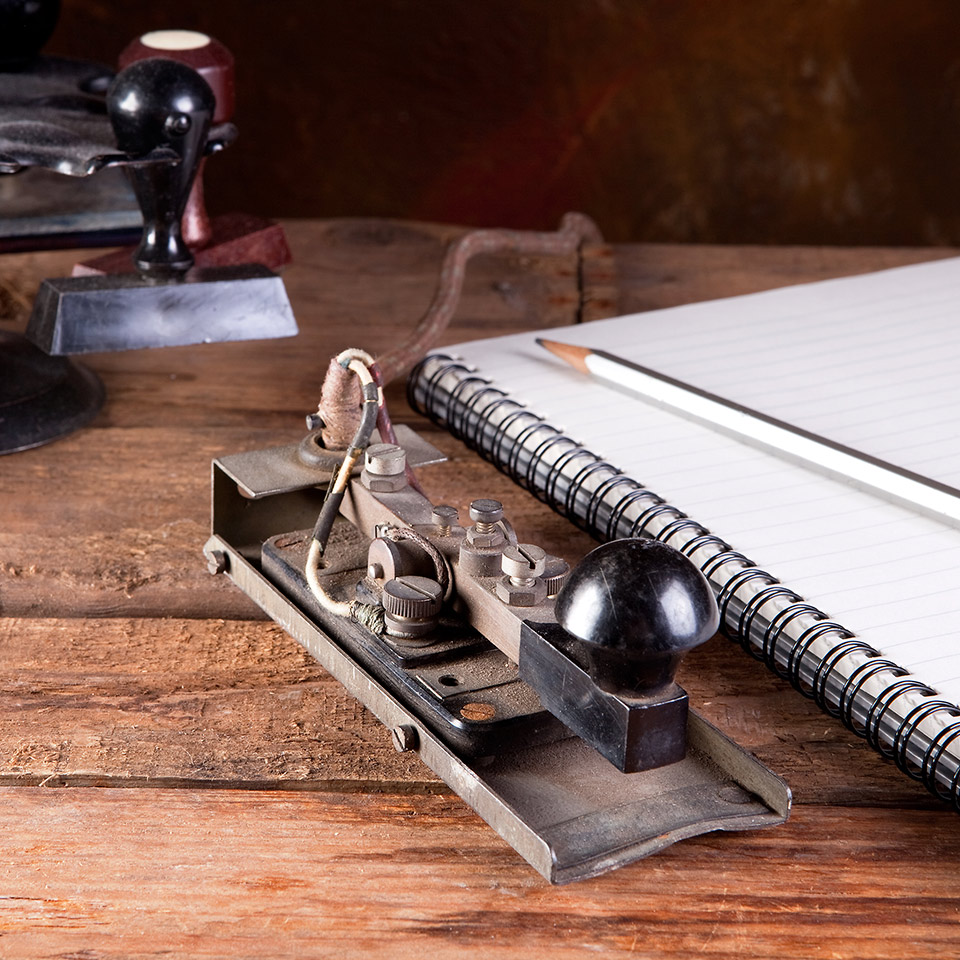 Vintage desk with antique telegraph, stamps, notebook and pen