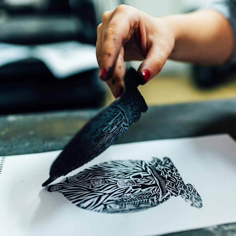 Artist lifting a piece of carved lino, leaving a patterned print on the page
