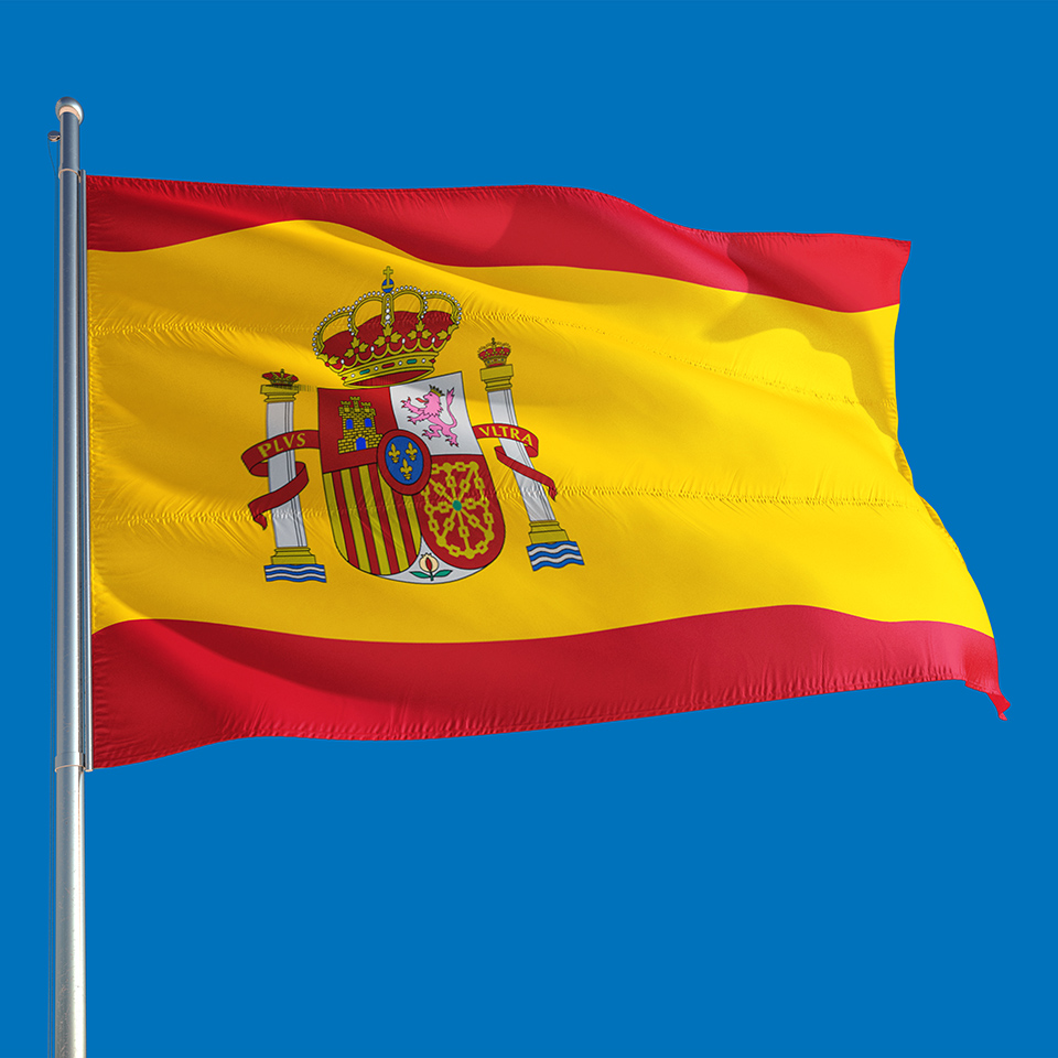 Spanish flag waving in the wind on a deep blue sky