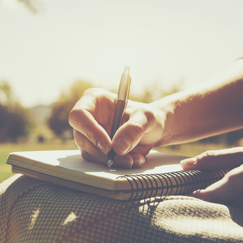 Man's hand writing in a journal