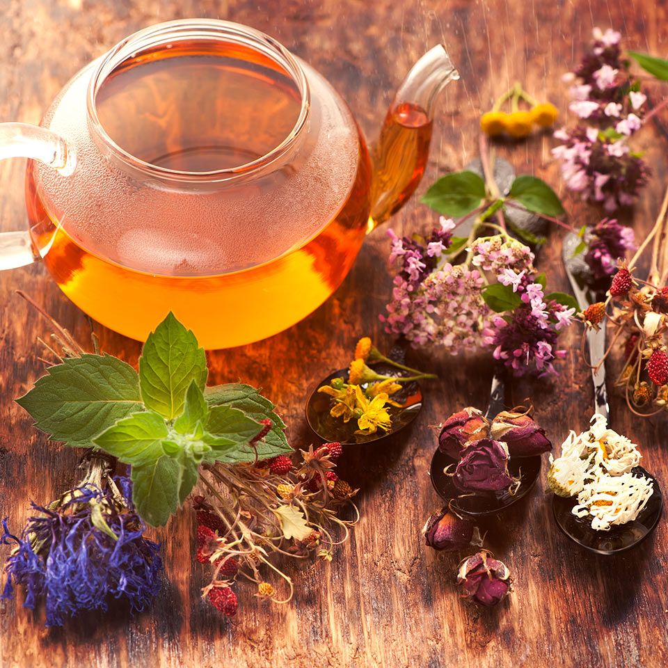 Herbal tea, herbs and flowers on a wooden background