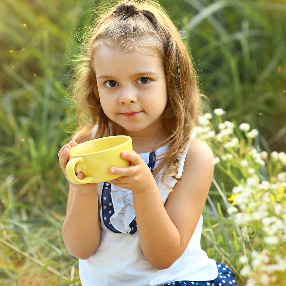 Girl sitting in a field, drinking herbal tea