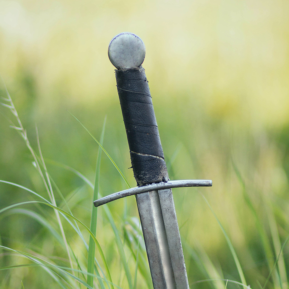 Sword stuck in the ground of a field
