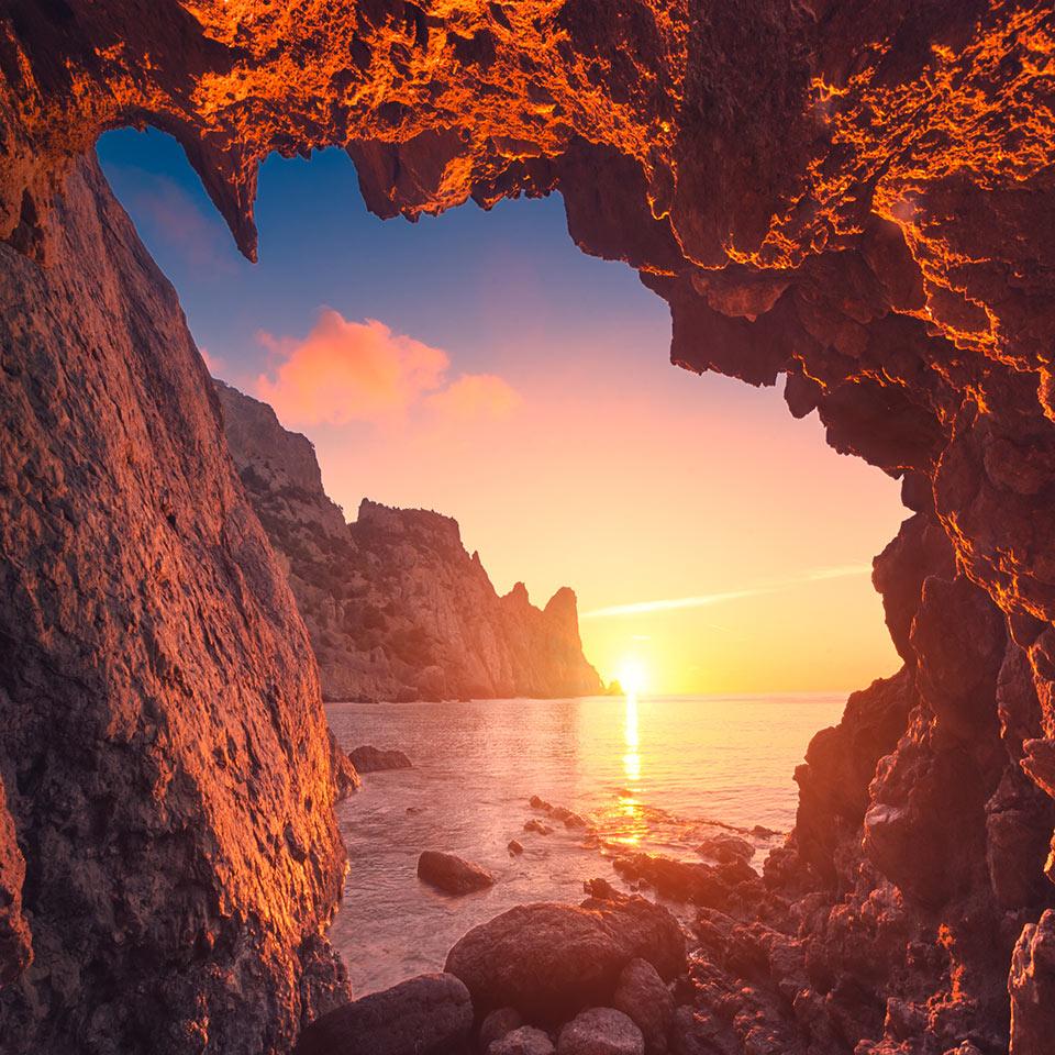 Beautiful sunrise from the mountain cave in a Crimea sea bay