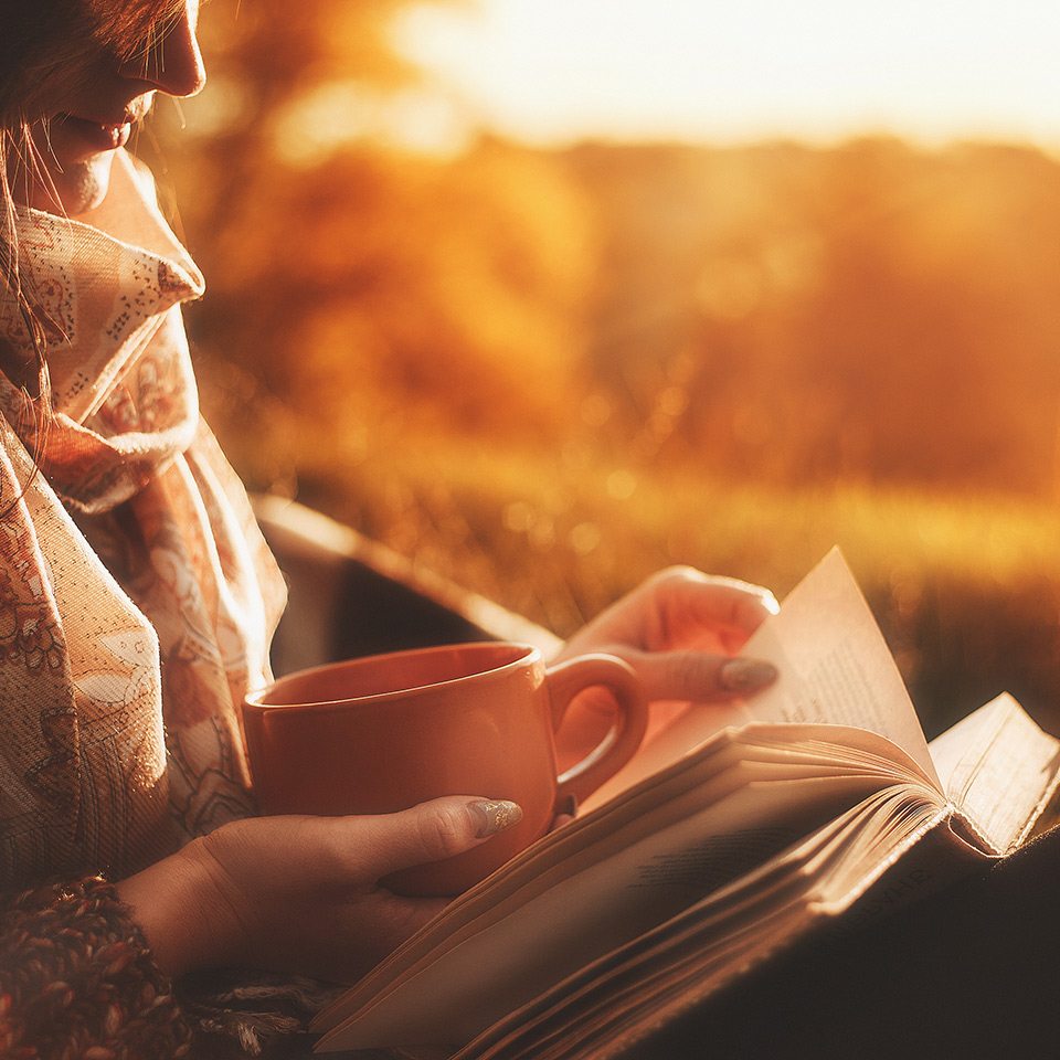 Woman sits near a tree in an autumn forest and holds a book and a cup with a hot drink in her hands