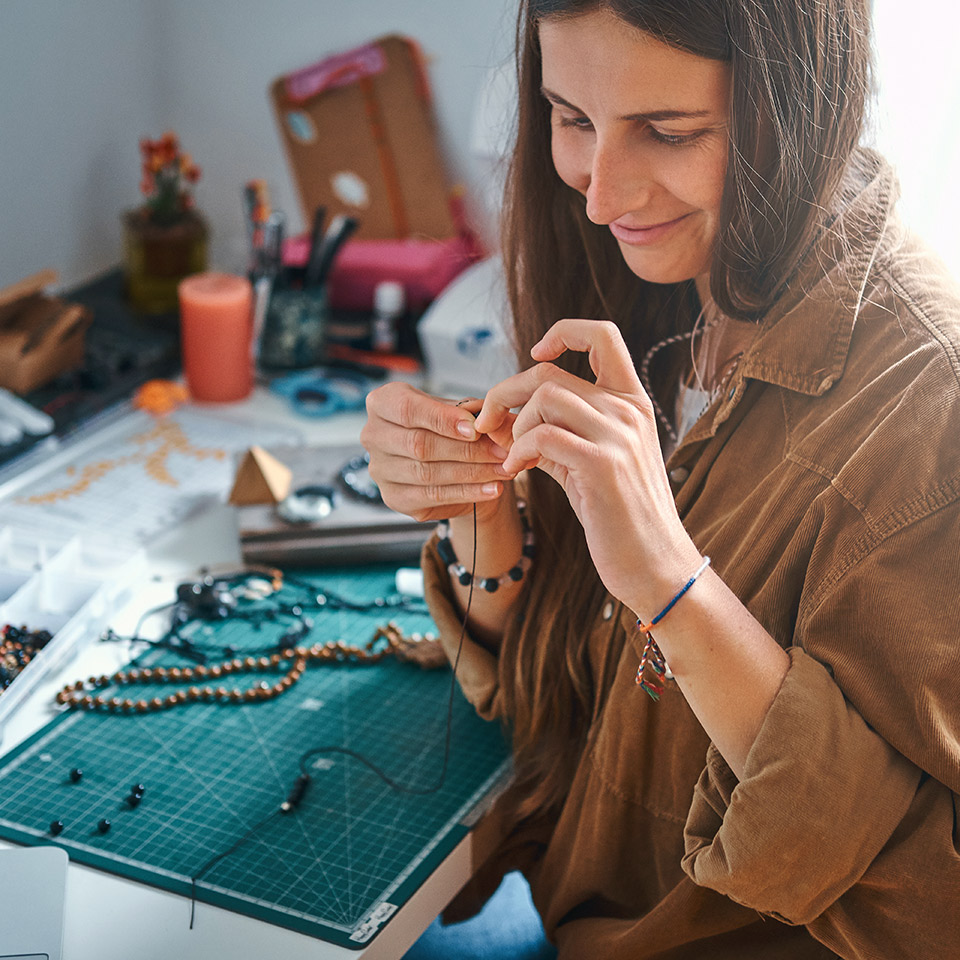 Woman working on beaded jewellery at a desk with jewellery making equipment on it