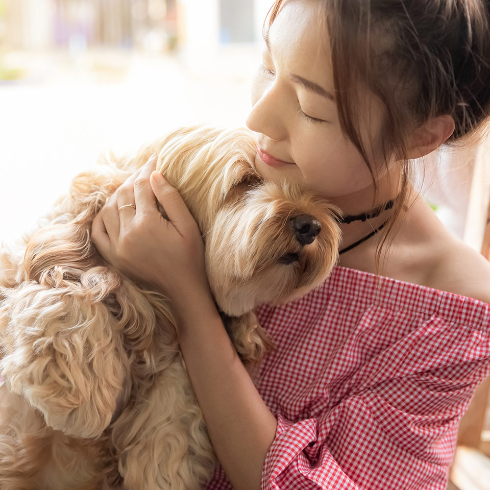 A young woman hugging her dog.