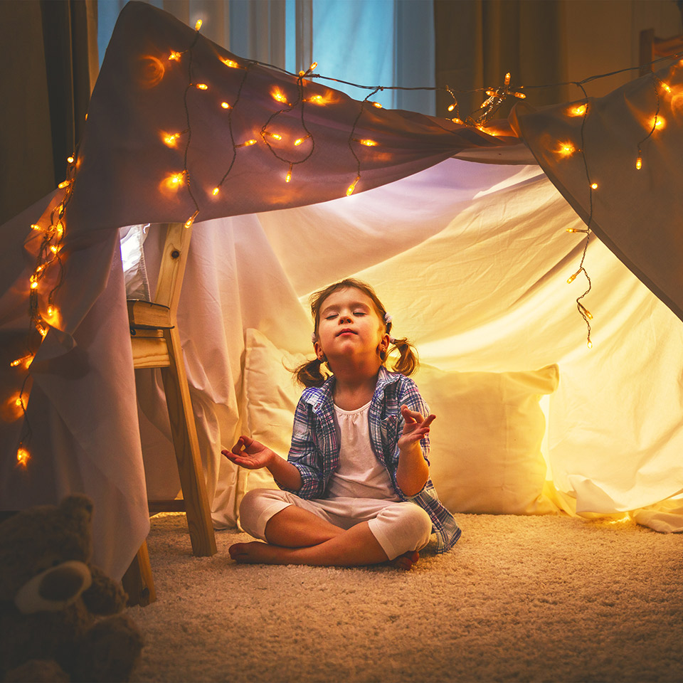 Girl meditating in a tent in her home