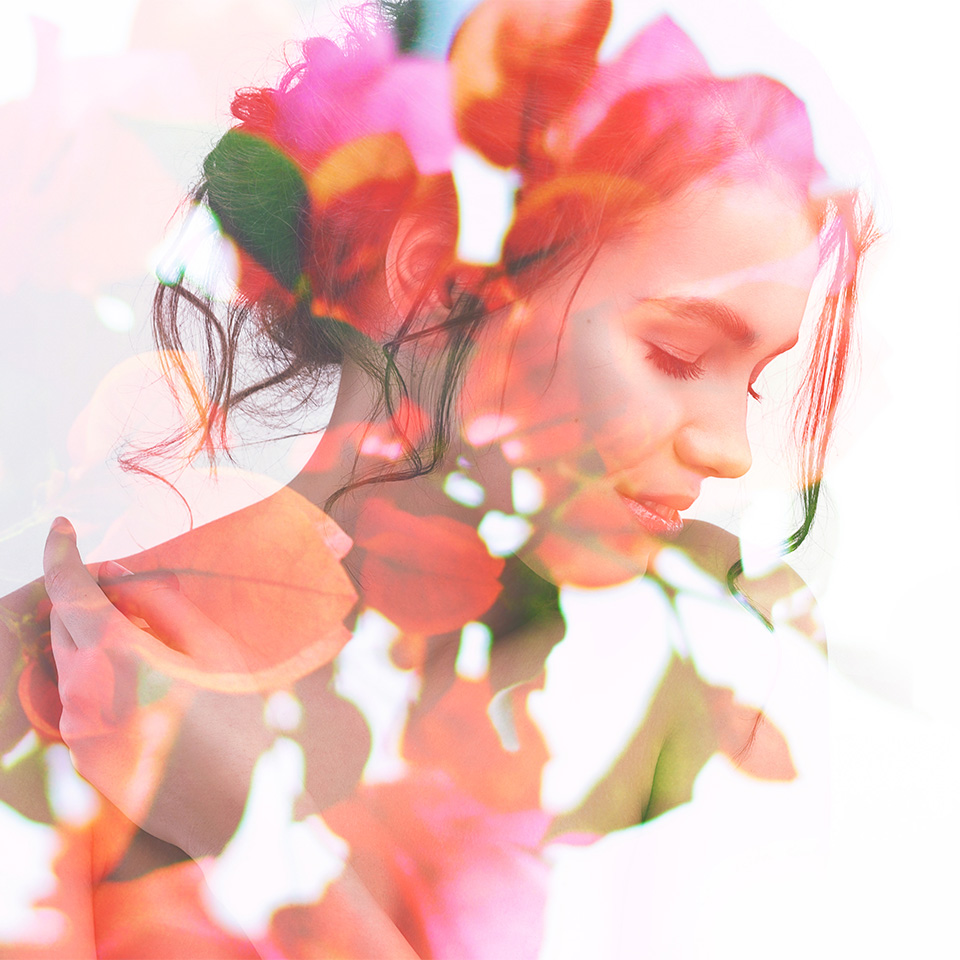 Double exposure portrait of young woman combined with photograph of bright spring garden flowers and leaves