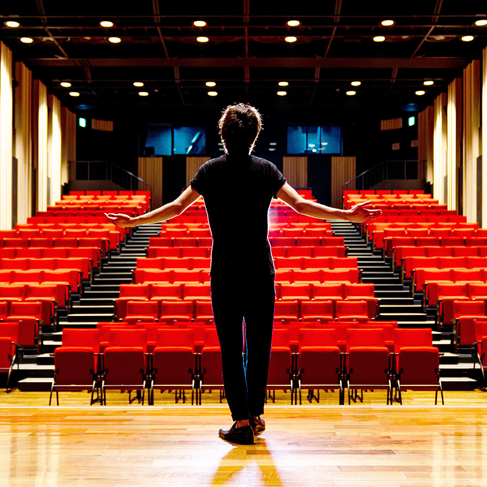 Young actor standing on the stage of a theatre