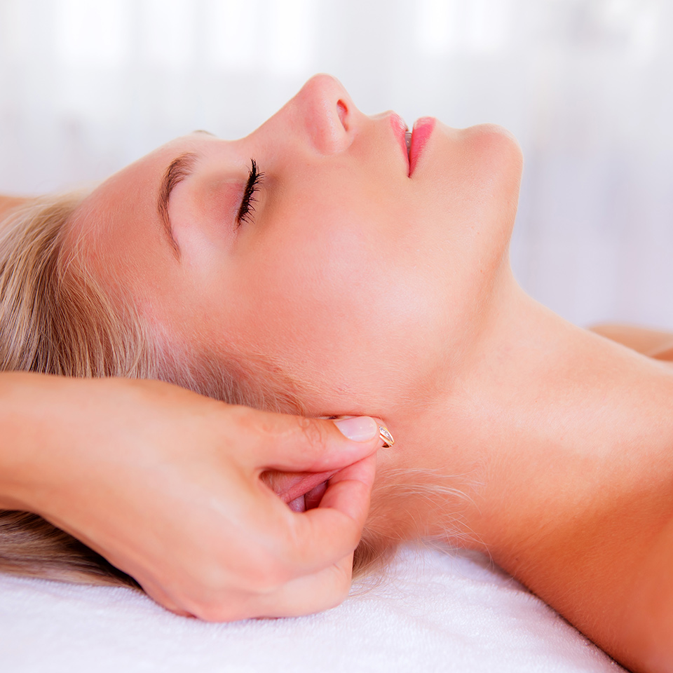 Woman lying down in a spa setting receiving auricular therapy
