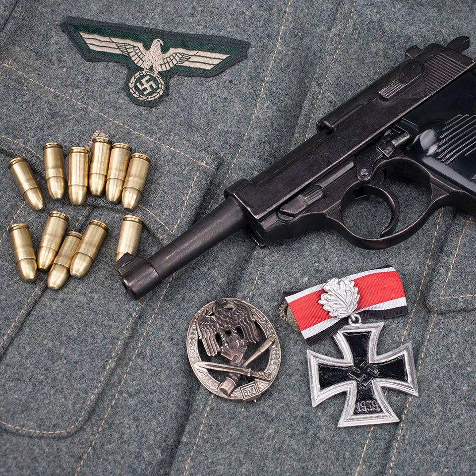 WWII-era Nazi German army 9mm semi-automatic pistol with Iron Cross award on army grey uniform background