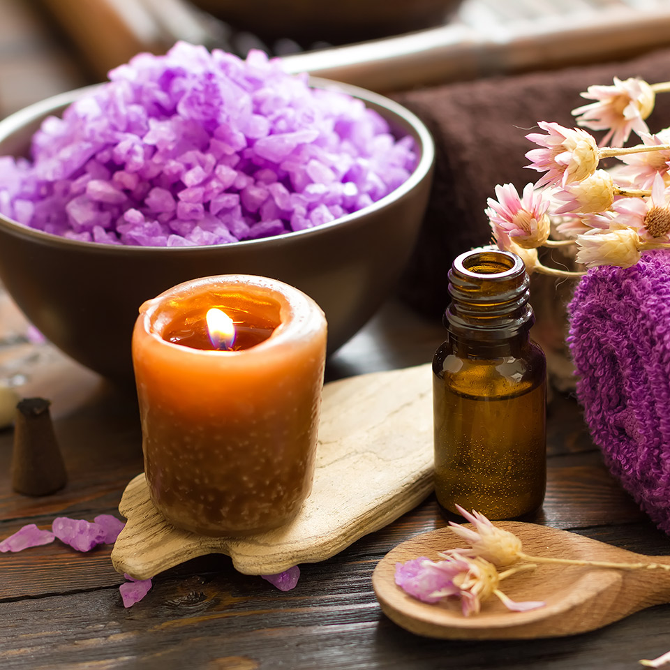 Aromatherapy products, including a candle and oil. Flowers, a bowl, and wooden spatulas are also visible in the image