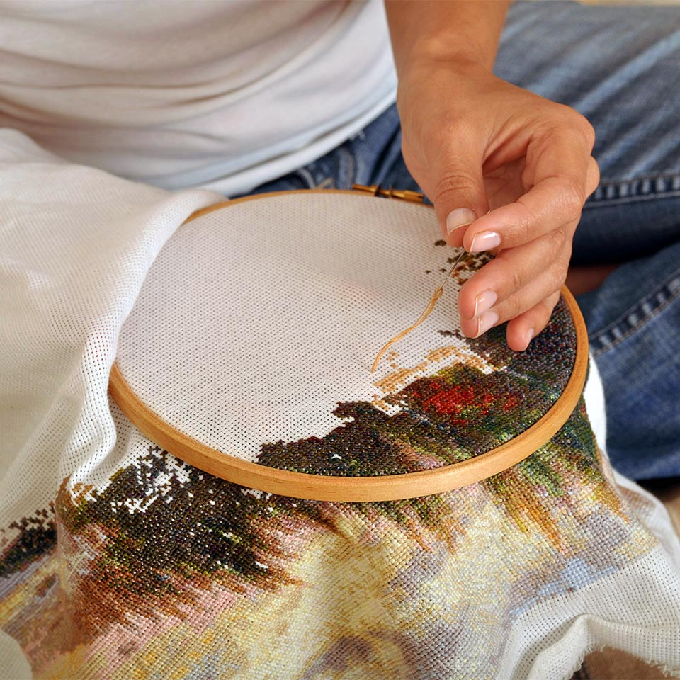 Woman working on a cross stitch hoop