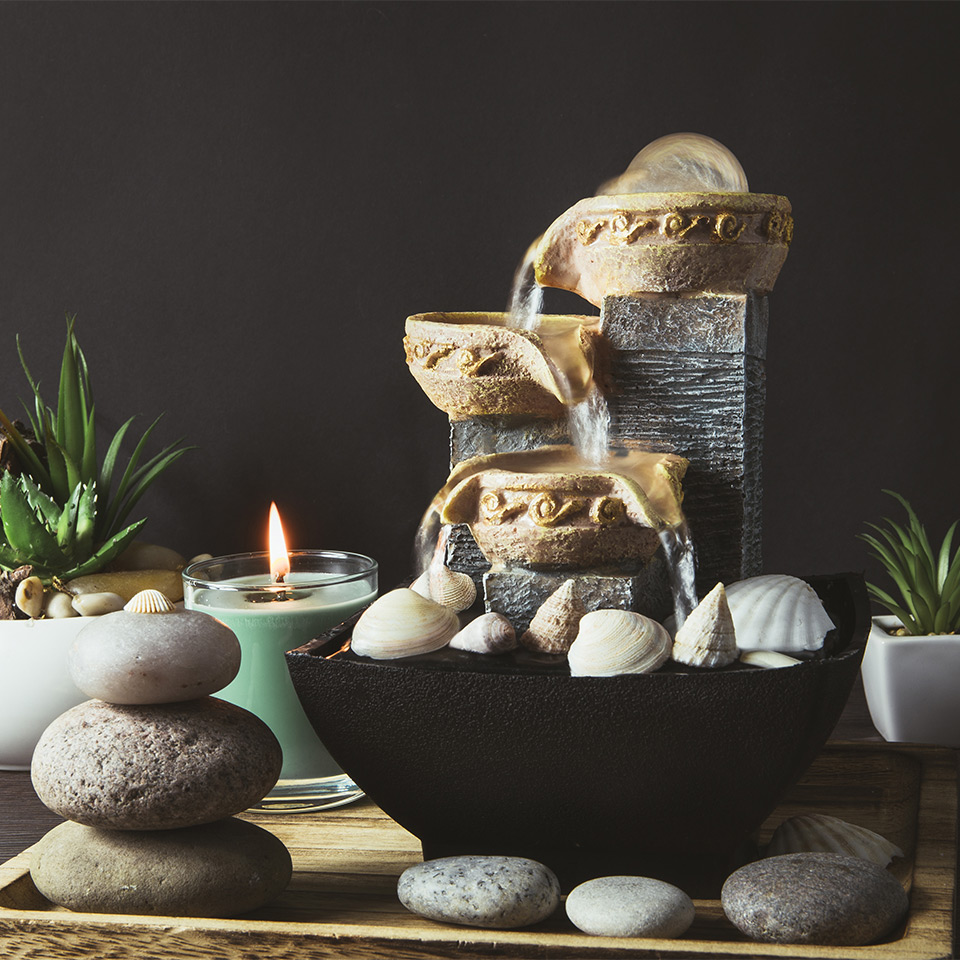 Pebbles, plants, and fountain arranged using feng shui principles