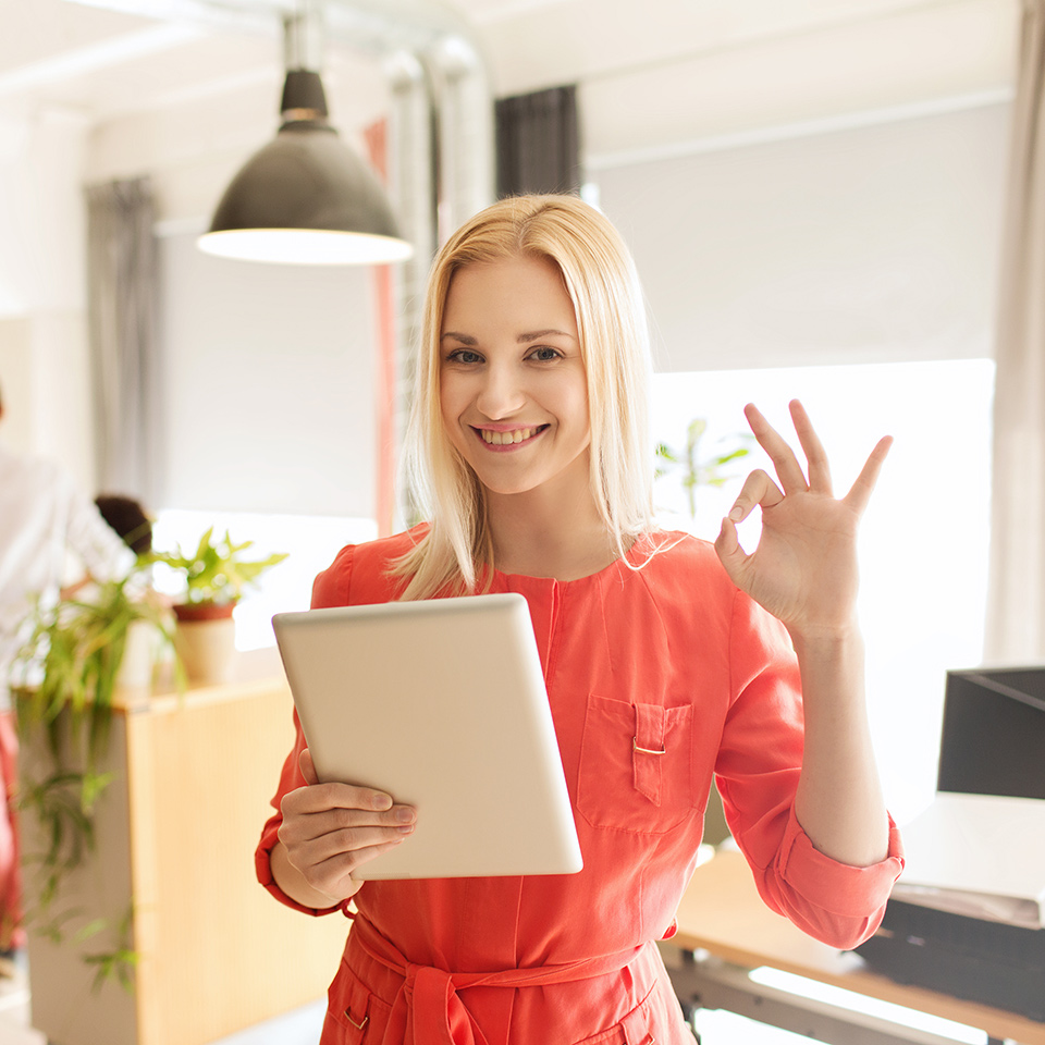Happy office worker with tablet pc computer showing ok hand sign