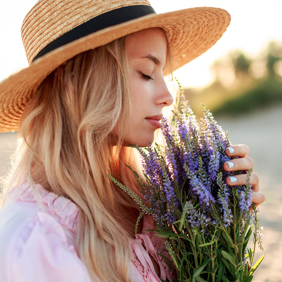 Woman in straw hat smelling flowers, the sun is setting behind her