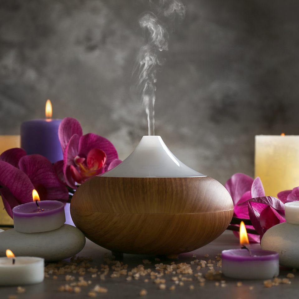 Essential oil diffuser, candles and flowers on a table