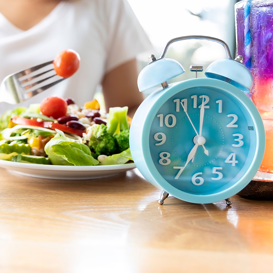 Blue clock and a woman eating a healthy meal