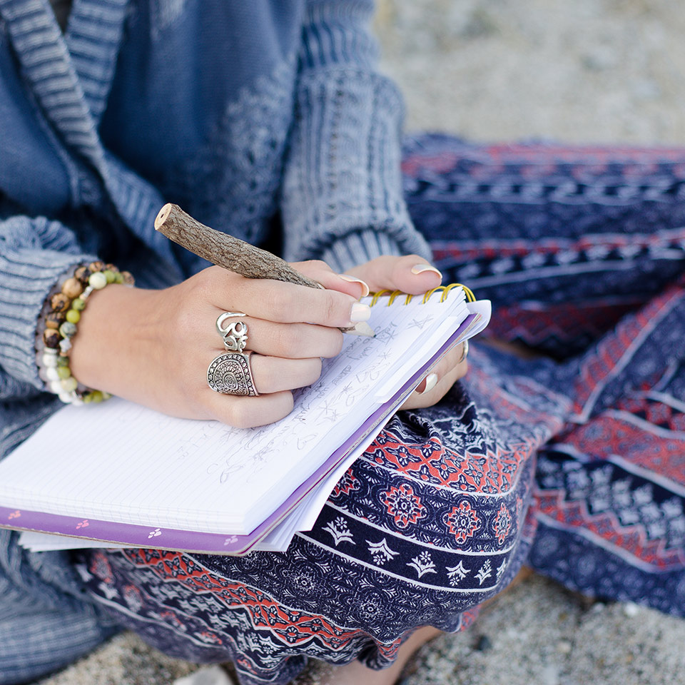 Woman sitting on a beach writing on a notebook