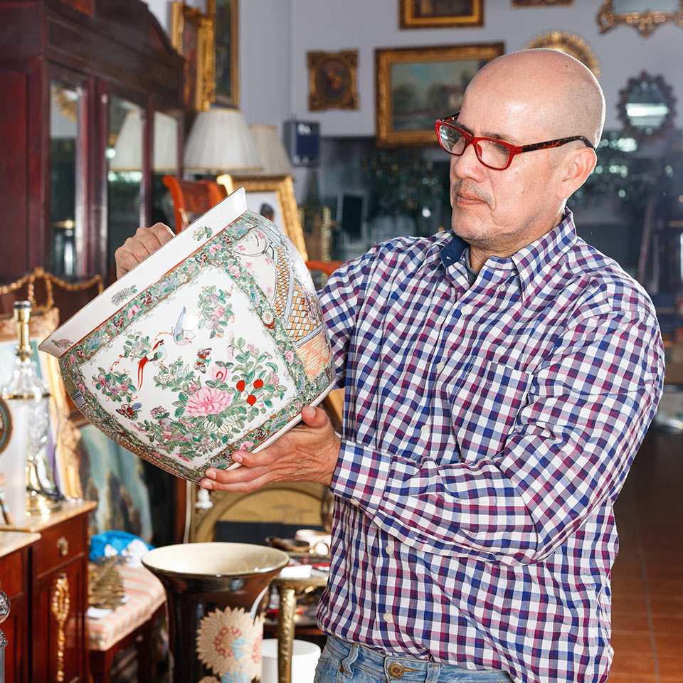 Man looking over a vase in an antiques shop
