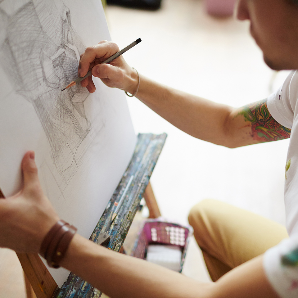 Artist at an easel drawing a portrait with a pencil