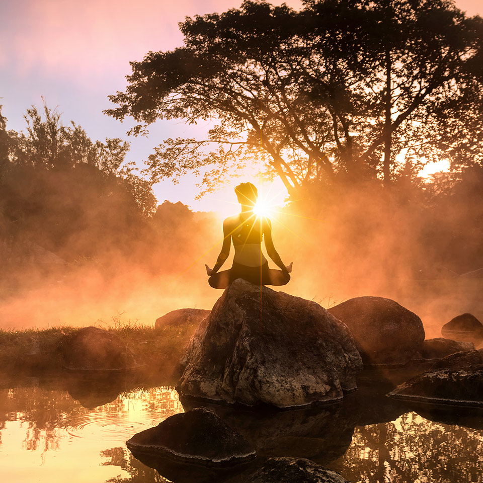 Young woman meditating by a misty lake at sunrise