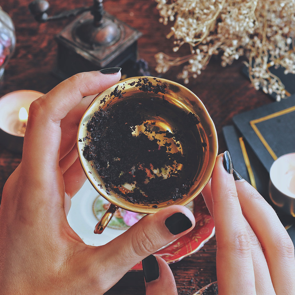 Hands holding a golden teacup for tea leaf tasseography. Black tea residue can be seen in the bottom of the cup.