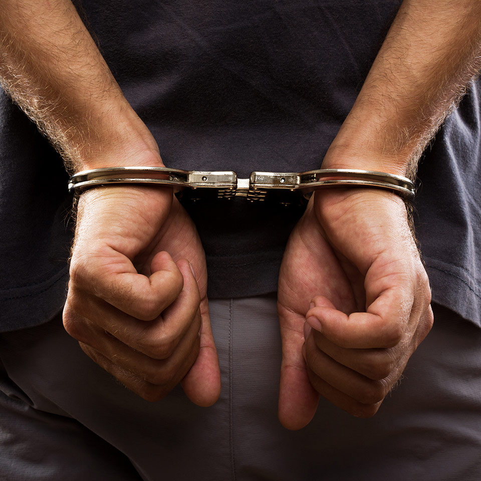 A pair of man's hands handcuffed at his back