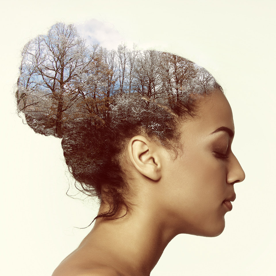 Double exposure of a woman in profile and a mountain forest