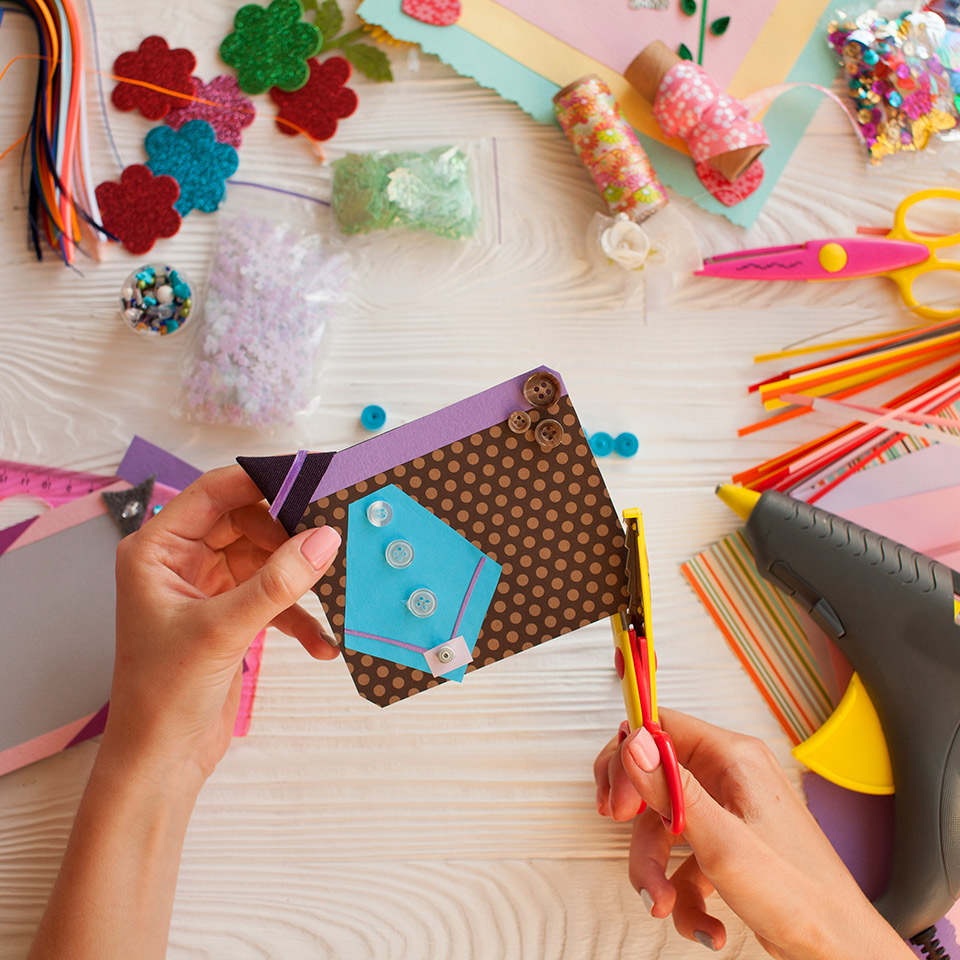 Pair of hands crafting a handmade card, surrounded by crafting materials and tools