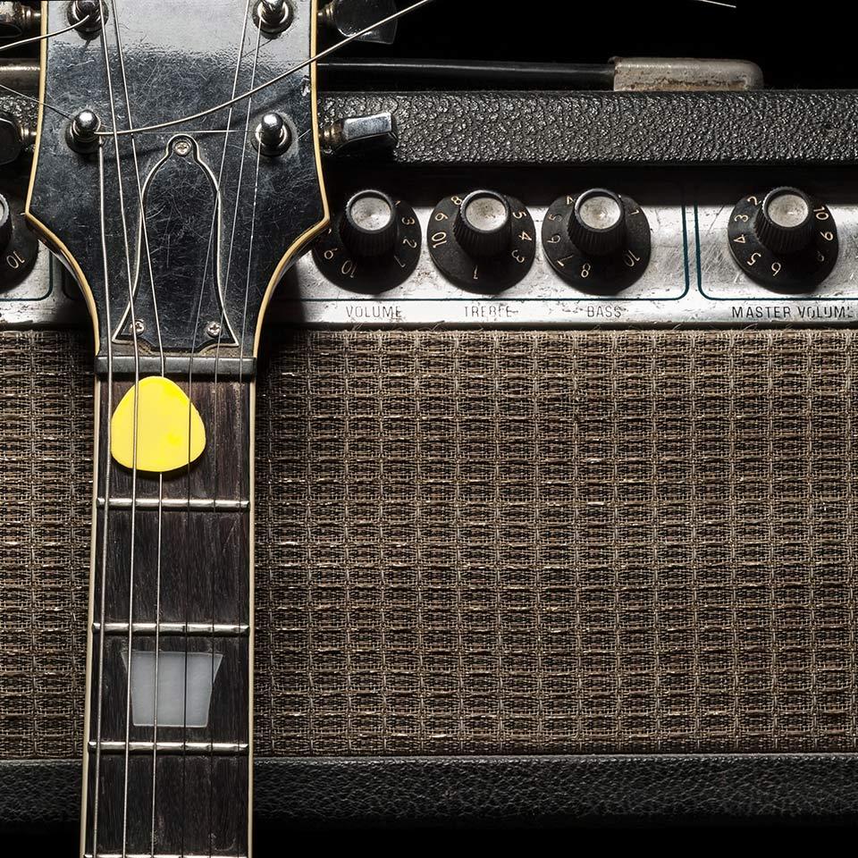 Electric guitar leant up against a guitar amplifier