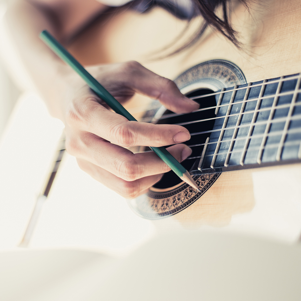 Songwriter playing guitar with a pencil in their hand