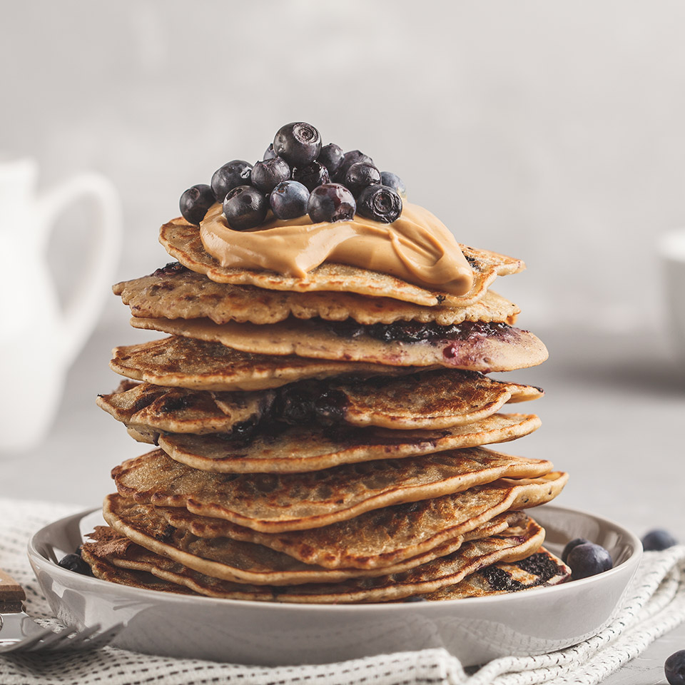 A stack of vegan pancakes with blueberries, peanut butter and syrup