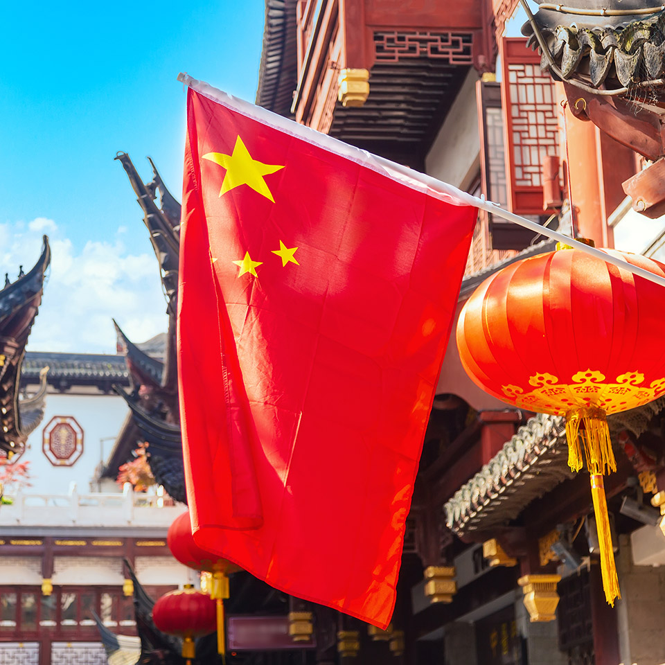 The red national flag of China against old, Chinese buildings at Yuyuan Garden in Shanghai, China