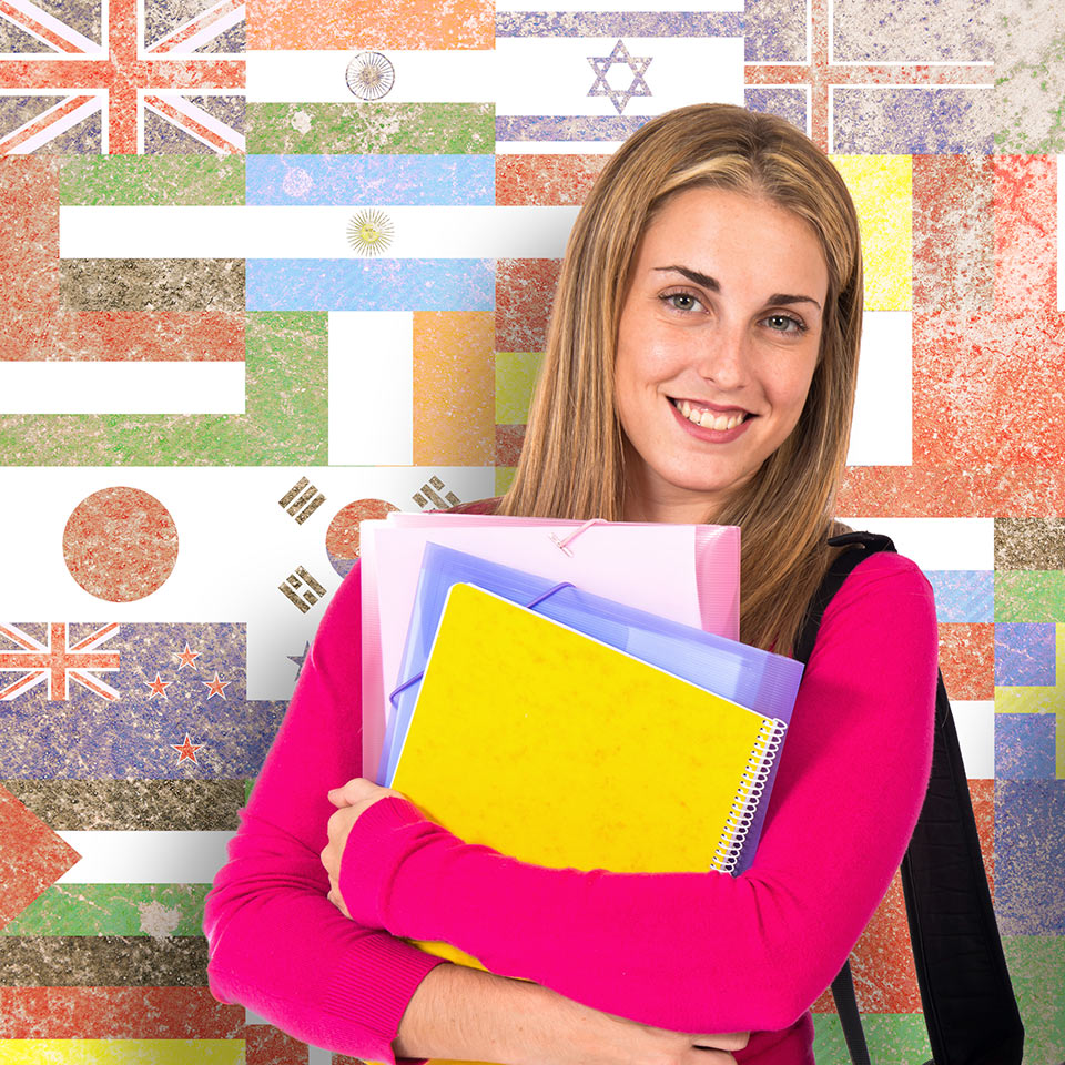 Student holding folders in front of a background made up of flags