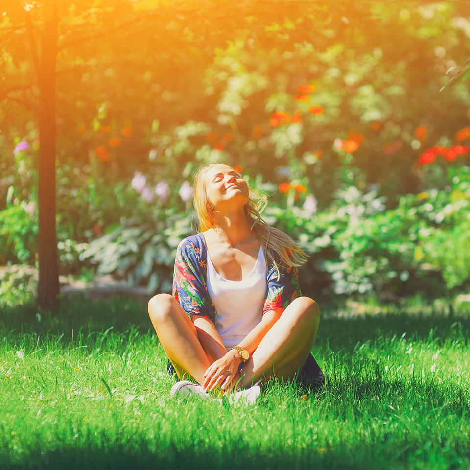 Happy woman sitting outdoors in a meditation position