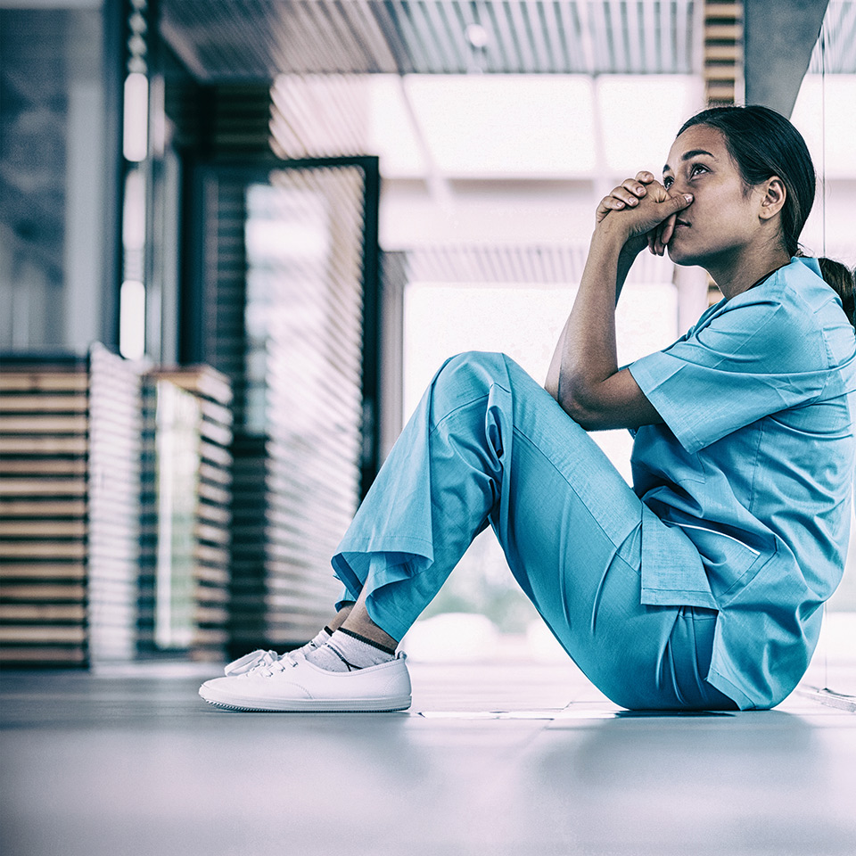 Anxious nurse sitting in hospital corridor